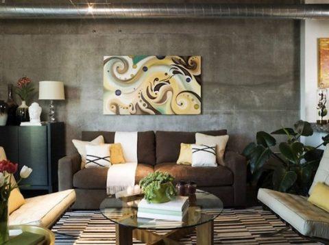 Бетонная стена в качестве фона для яркого панно и дивана