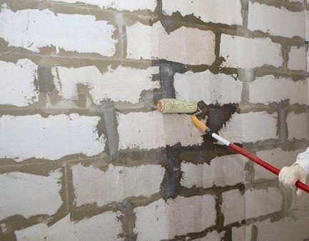 Нанесение грунтовки на стену из газобетона