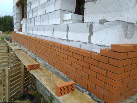 Облицовка фасада дома из пенобетонных блоков при помощи кирпича
