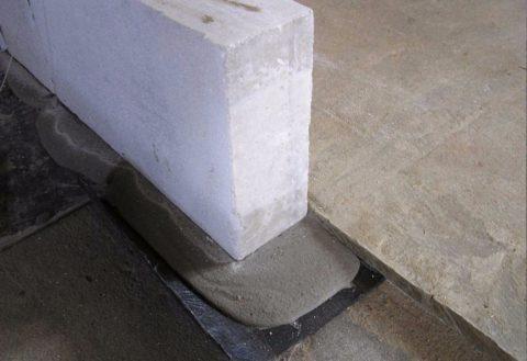 Укладка первого ряда. На фото хорошо видны гидроизоляция и цементно-песчаная подушка