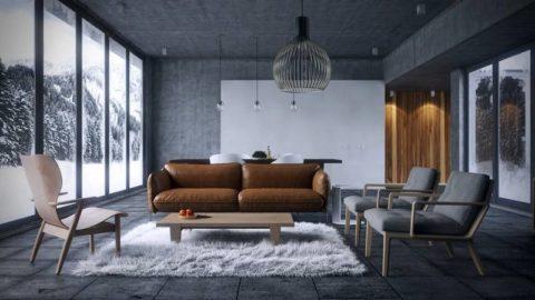 Меховой ковер на полу гостиной с бетонными поверхностями, вместе с кожаным диваном дают тепло и атмосферу уюта