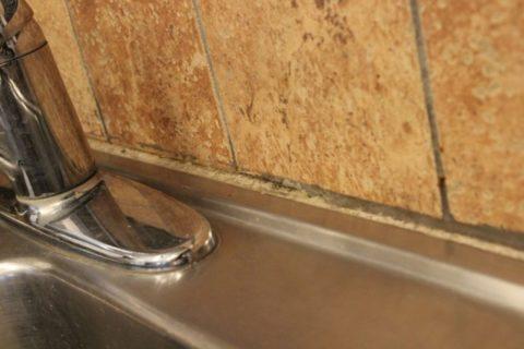 Очистка пространства за раковиной в месте стыка со стеной