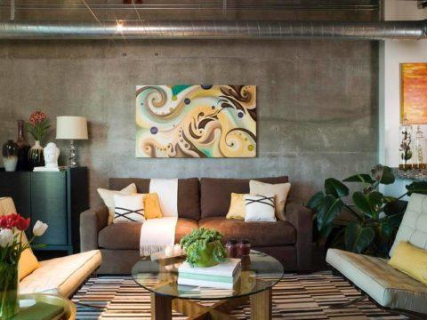 Уютный интерьер гостиной с бетонной стеной