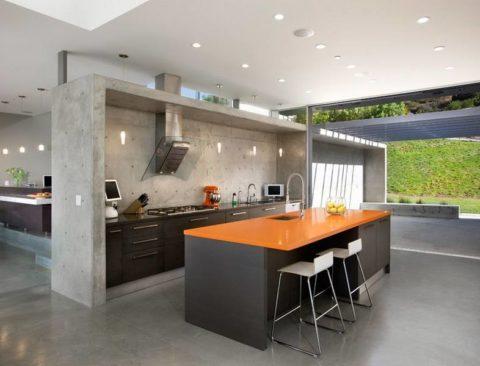 Яркая глянцевая столешница в бетонной кухне