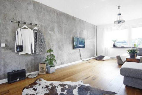 За счет «мягких» акцентов интерьер с бетонной стеной выглядит теплее