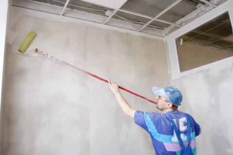 Грунтовку на стену удобнее наносить валиком с длинной ручкой