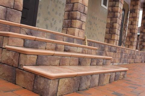 Крыльцо и колонны здания облицованы плиткой на основе бетона, выполненной под натуральный камень, а придомовая территория выложена бетонной брусчаткой.
