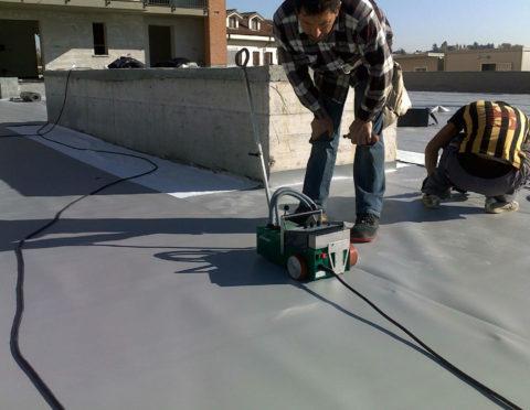 На фото процесс укладки ПВХ мембран для гидроизоляции бетонной крыши
