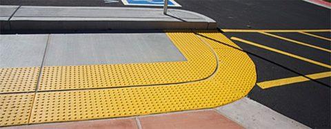 Полоса тактильной плитки на дороге помогает ориентироваться людям с ограниченным зрением