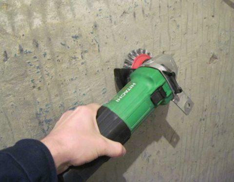 Удаление краски с бетонной стены при помощи шлифовальной машинки с металлической насадкой
