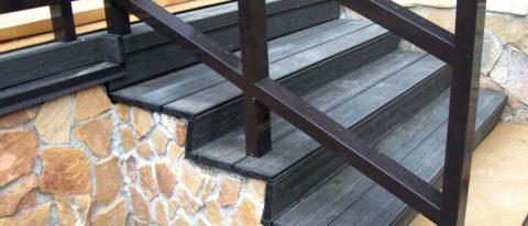 Бетонные ступени крыльца, обшитые террасной доской, окрашенной в черный цвет