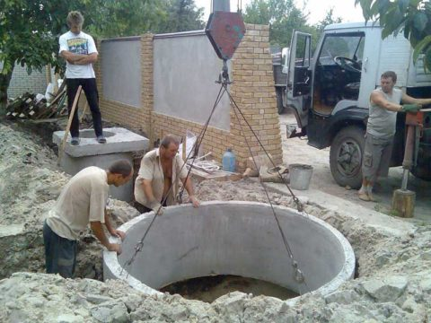 Установка бетонных колец при помощи крана