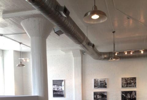 Вентиляционные каналы и открытая электропроводка на фоне бетонного потолка смотрятся очень органично
