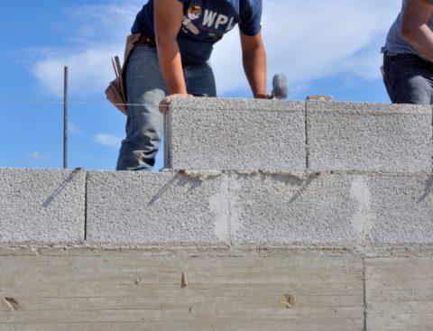 На фото – процесс возведения стены из
