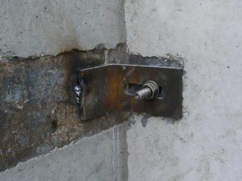 Прежде чем закрепить на бетонной колонне стеновую панель, к закладной приваривают металлический уголок