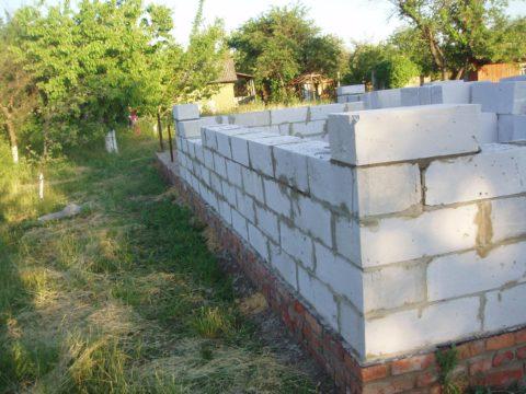 Технология постройки дома из газобетона – стены стоят на цоколе из красного кирпича
